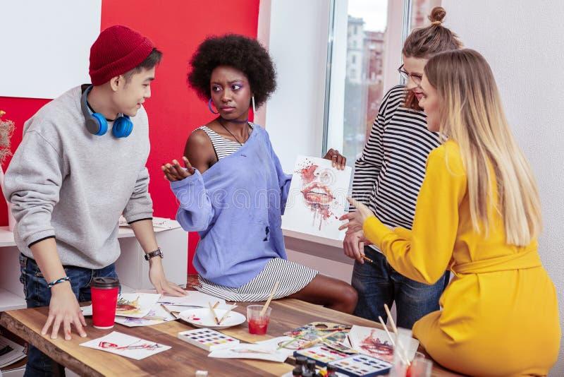 Vier Studenten, die Diskussionen hinsichtlich der kreativen Malerei haben lizenzfreies stockfoto