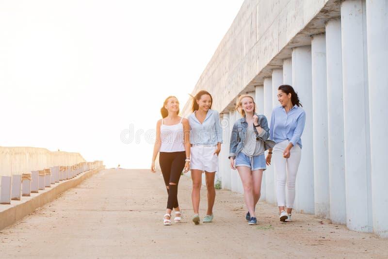 Vier Studenten, die hinunter Gehweg gehen lizenzfreies stockfoto
