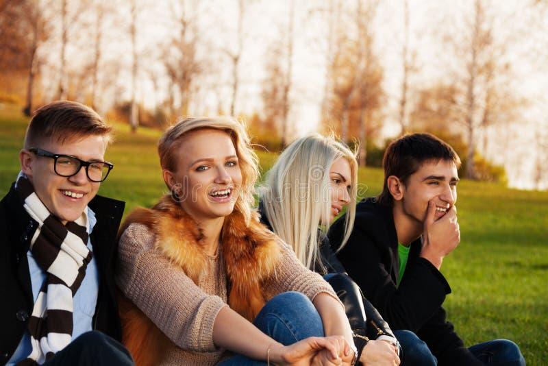 Vier Studenten, die Spaß im Park haben stockbild