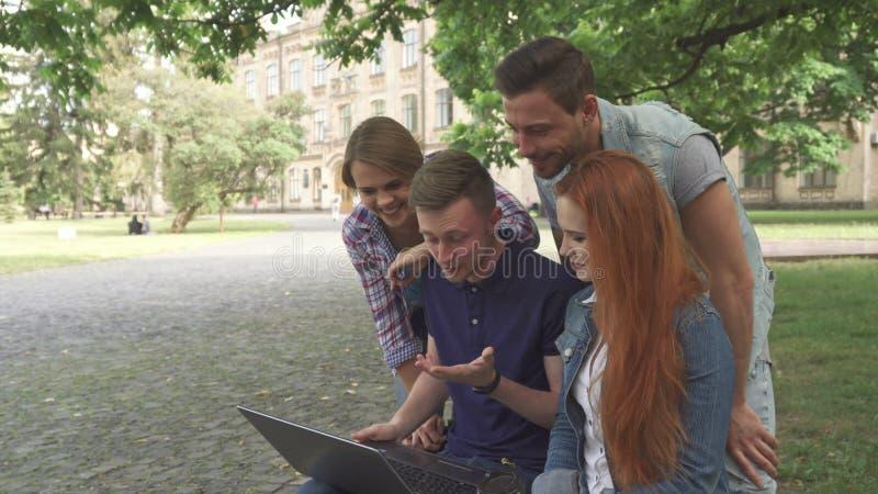 Vier studenten lachen bij wat zij op laptop op campus zien royalty-vrije stock afbeeldingen