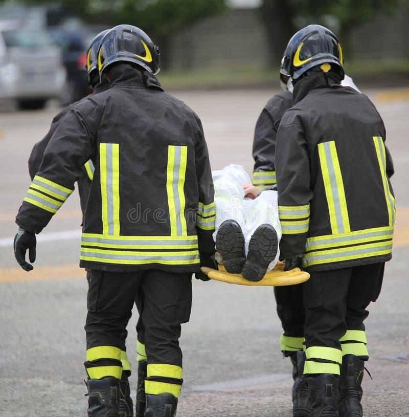 Vier tapfere Feuerwehrmänner transportieren verletzt mit einer Bahre stockfoto