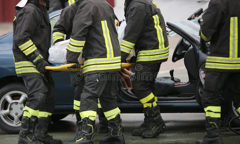 Vier tapfere Feuerwehrmänner transportieren verletzt mit einer Bahre stockbild
