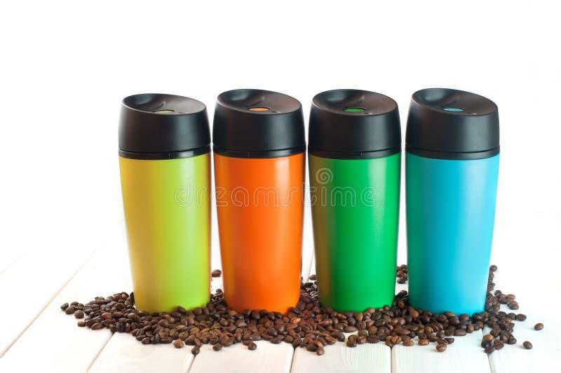 Vier thermosfles overvalt dichtbij koffiebonen op de witte achtergrond royalty-vrije stock afbeelding