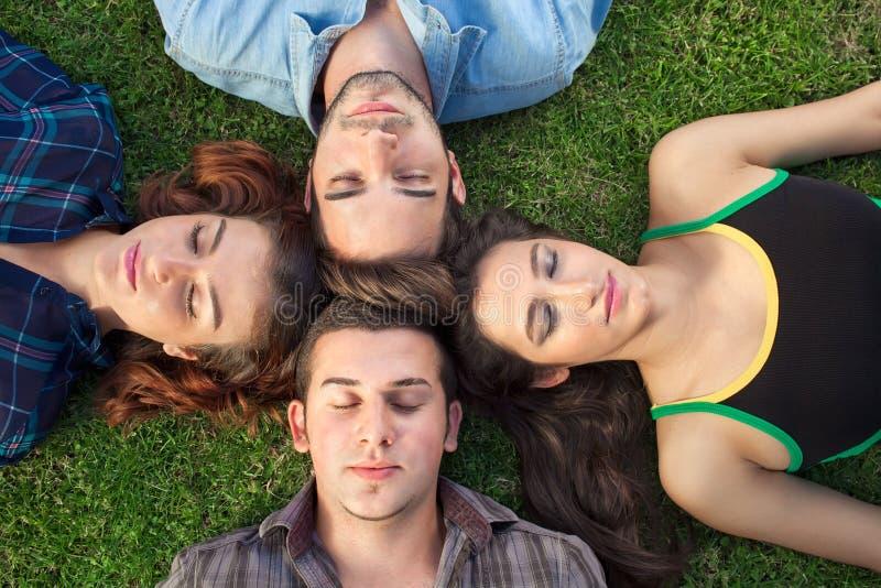 Vier tieners die op het gras ontspannen royalty-vrije stock foto