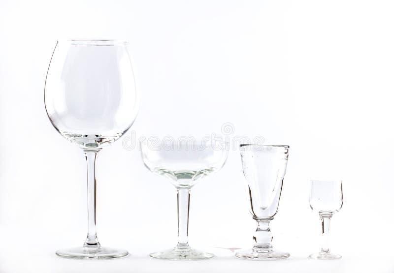 Vier transparente elegante Kristallgläser für Cocktails zeichneten neben einander auf einem weißen Hintergrund stockfotos