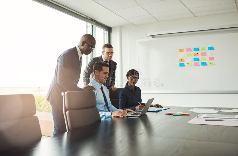 Vier van jonge bedrijfsmensen in bureau met grafiek royalty-vrije stock afbeelding