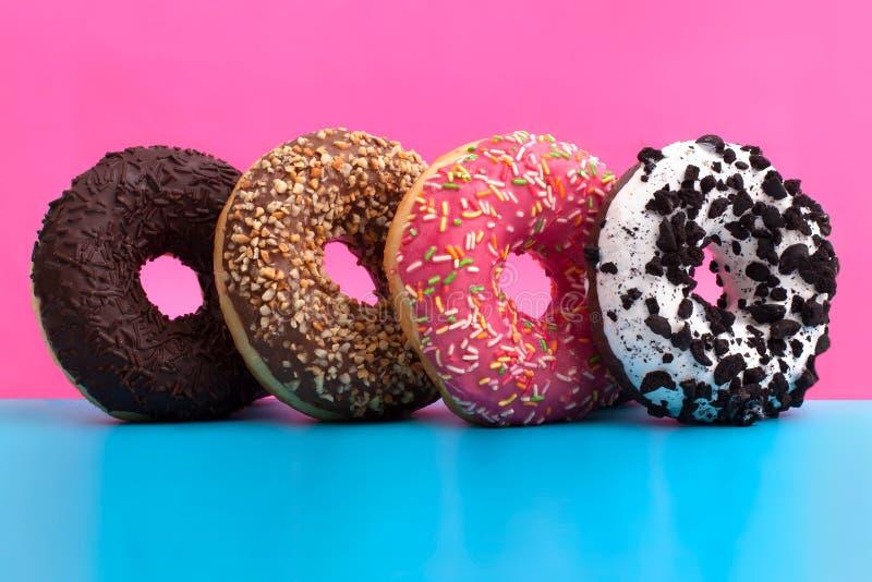 Vier verschillende donuts op blauwe en roze achtergrond royalty-vrije stock afbeeldingen
