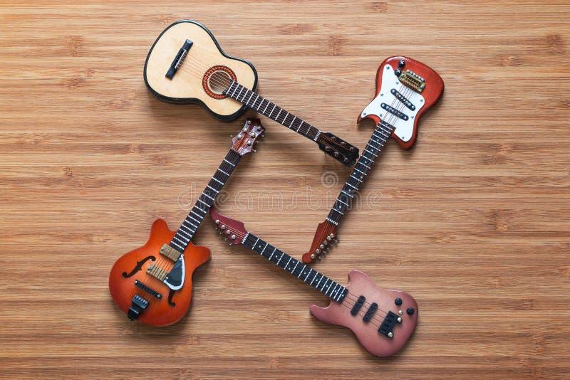 Vier verschillende elektrische en akoestische gitaren op een houten achtergrond Stuk speelgoed gitaren Het concept van de muziek royalty-vrije stock foto