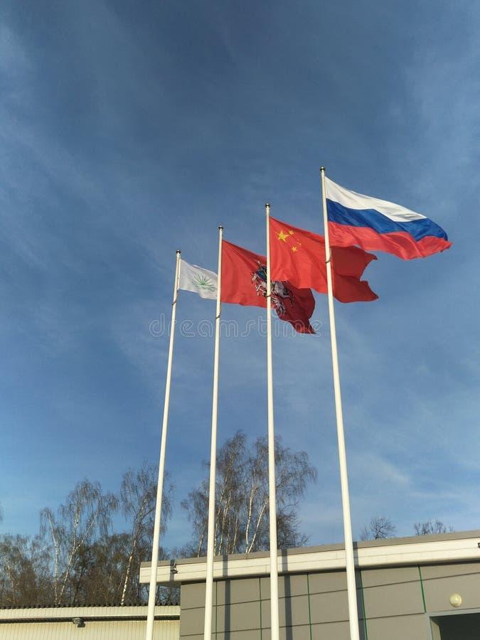 Vier vlaggen fladderen in de wind tegen de heldere blauwe hemel, Chinees rood met vijf sterren, Russische tricolour, de vlag van royalty-vrije stock foto
