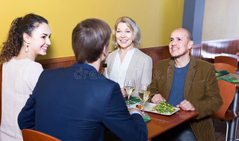 Vier volwassenen die met wijn en diner in restaurant lachen stock afbeelding