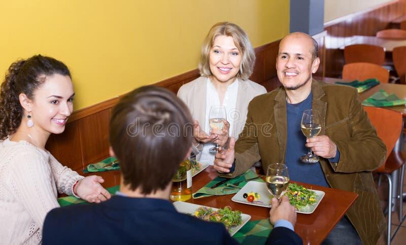 Vier volwassenen die met wijn en diner in restaurant lachen royalty-vrije stock afbeelding