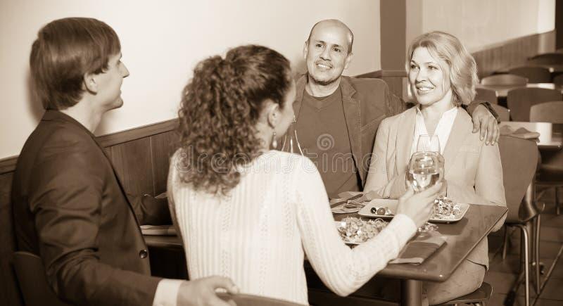 Vier volwassenen die met wijn en diner in restaurant lachen stock foto