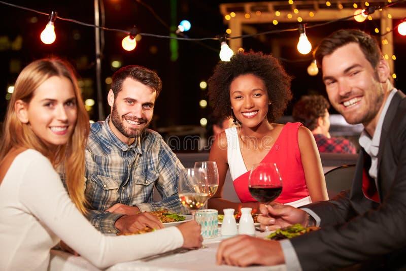 Vier vrienden die diner eten bij dakrestaurant stock foto's