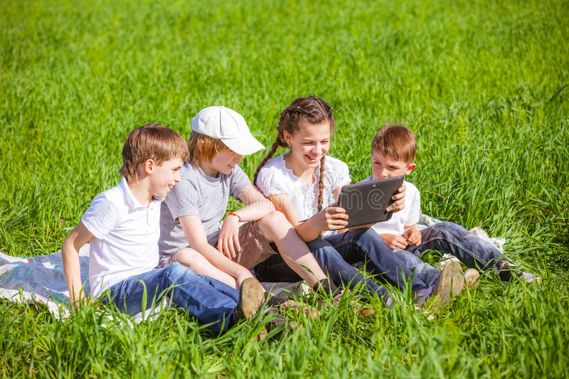 Vier vrienden die op gras zitten stock afbeeldingen