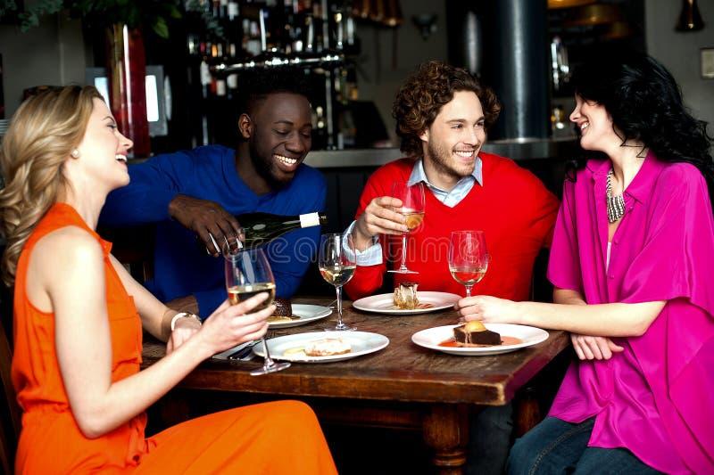 Vier vrienden die van diner genieten bij een restaurant stock afbeeldingen