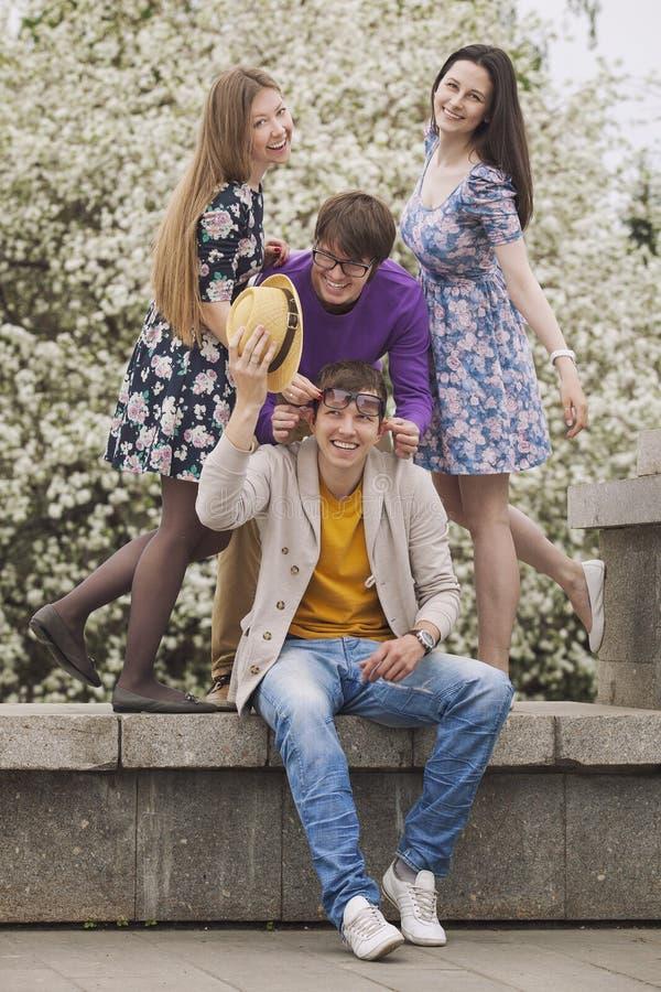 Vier vrienden in een Park die gelukkig glimlachen stock fotografie
