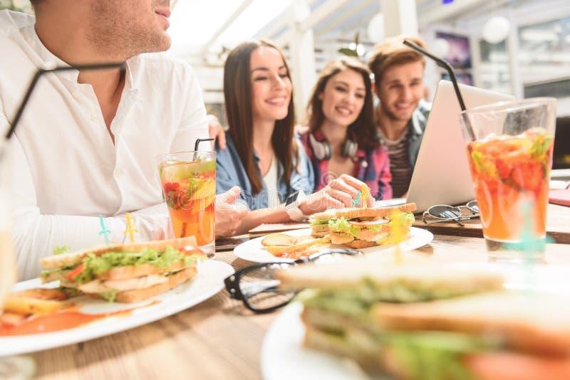 Vier vrienden in koffie winkelen gebruikend laptop royalty-vrije stock afbeeldingen