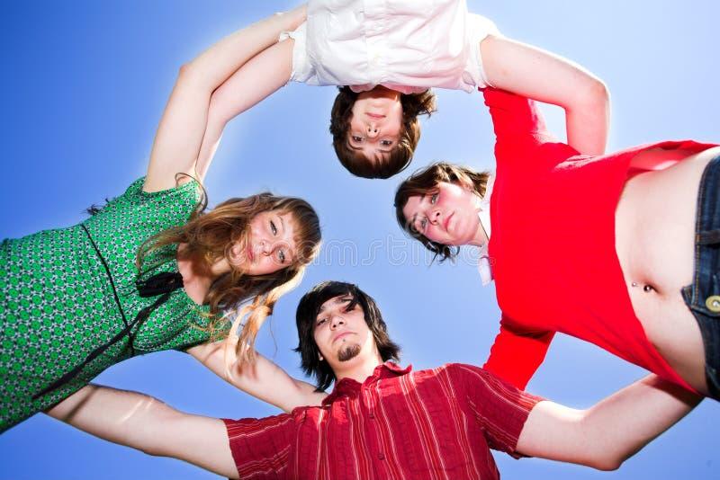 Vier vrienden omcirkelen stock fotografie