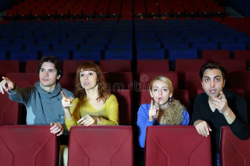 Vier vrienden verbazen en richten vinger op het scherm stock afbeelding