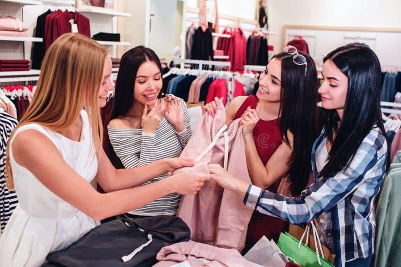 Vier vrienden verenigen en houden zich één roze sweatshirt De meisjes bekijken het en glimlachen Zij zijn zeer royalty-vrije stock afbeeldingen