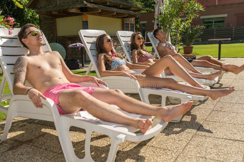 Vier vrienden zonnebaden op de zonlanterfanters op het strand stock afbeelding