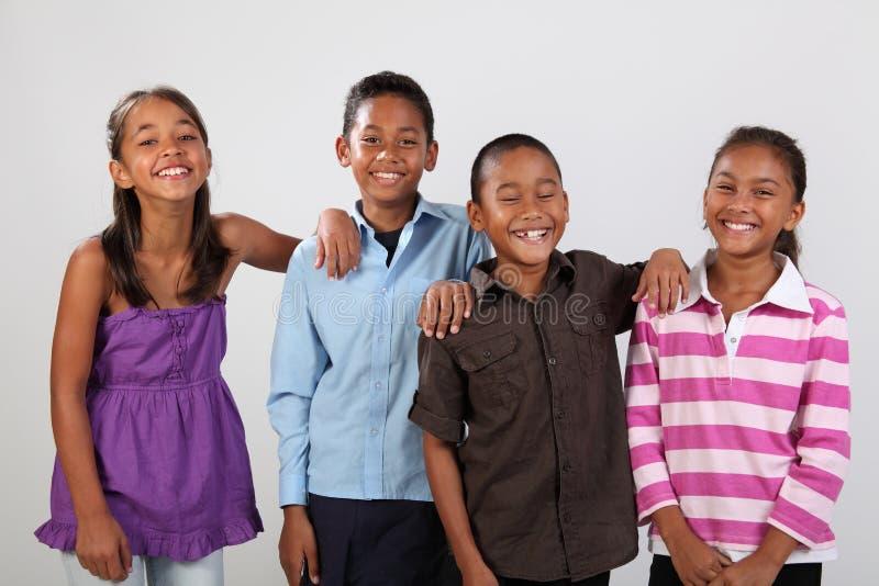 Vier vrolijke schoolvrienden delen gelukkig gelach stock afbeeldingen