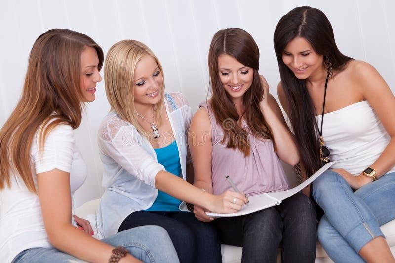 Vier vrouwelijke vrienden die een omslag bekijken royalty-vrije stock fotografie