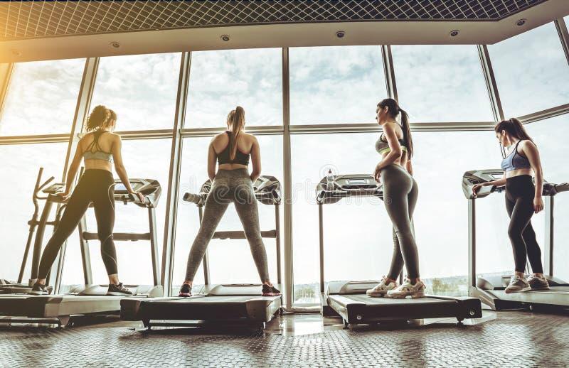 Vier vrouwen die oefeningen op de tredmolen doen stock foto