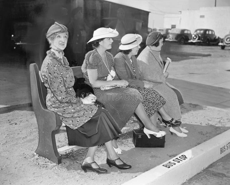 Vier vrouwen die op een bank zitten die op de bus wachten (Alle afgeschilderde personen leven niet langer en geen landgoed bestaa royalty-vrije stock foto's