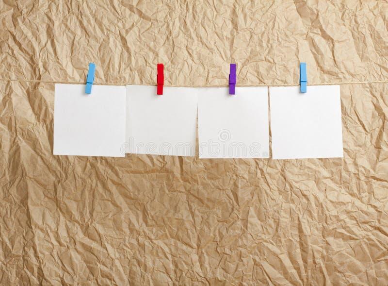 Vier weiße leere Anmerkungen, die an der Wäscheleine auf Kraftpapier hängen stockbilder