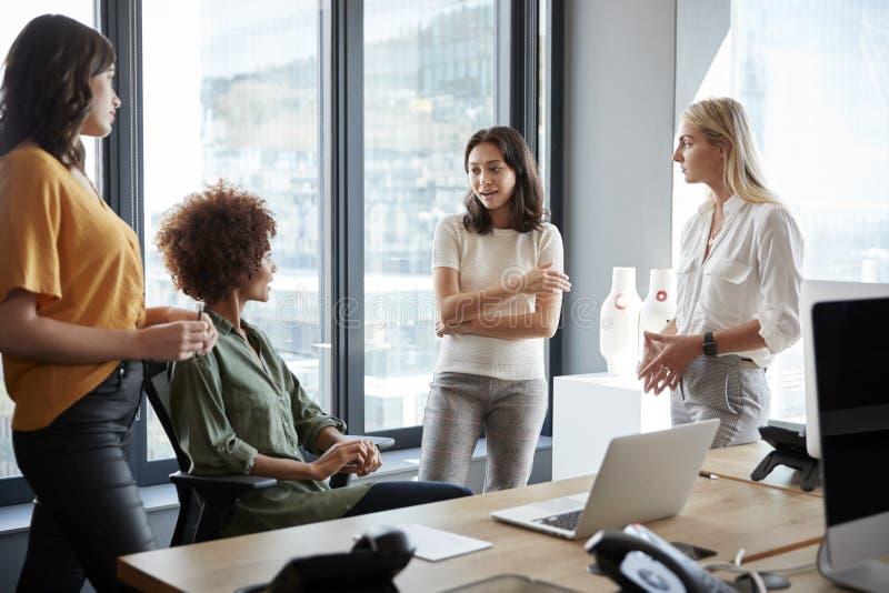 Vier weibliche Kollegen in der Diskussion an einem Schreibtisch in einem kreativen Büro, drei Viertellänge stockbilder