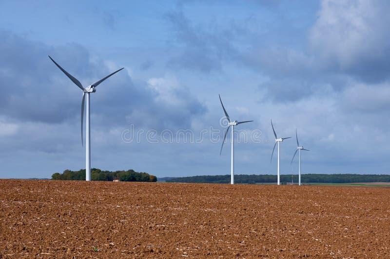 Vier windturbines op een gebied onder bewolkte blauwe hemel stock foto's