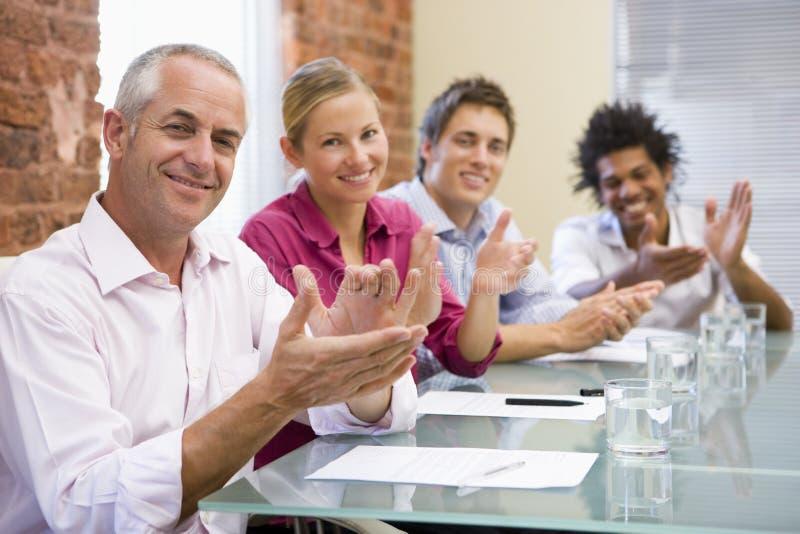 Vier Wirtschaftler beim Sitzungssaalapplaudieren lizenzfreie stockfotos