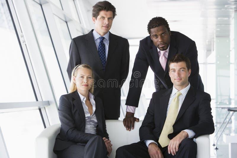 Vier Wirtschaftler in der Bürovorhalle lizenzfreie stockbilder