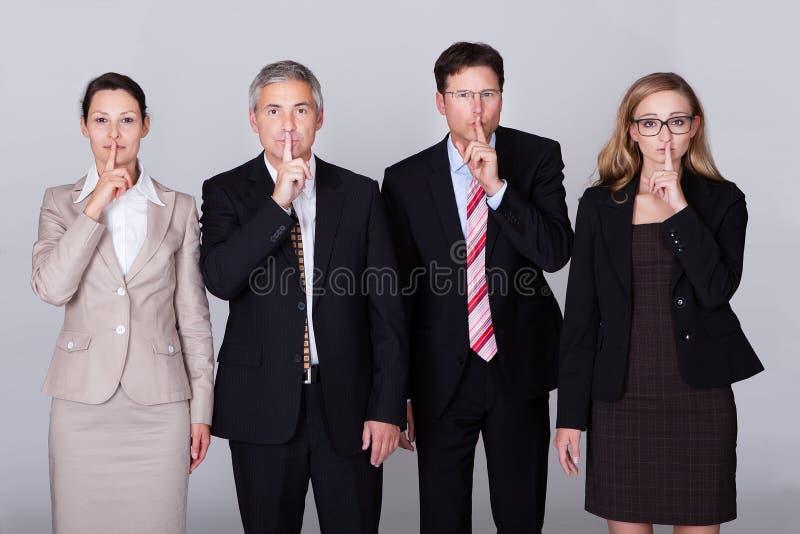 Vier Wirtschaftler, die für Ruhe gestikulieren lizenzfreie stockbilder