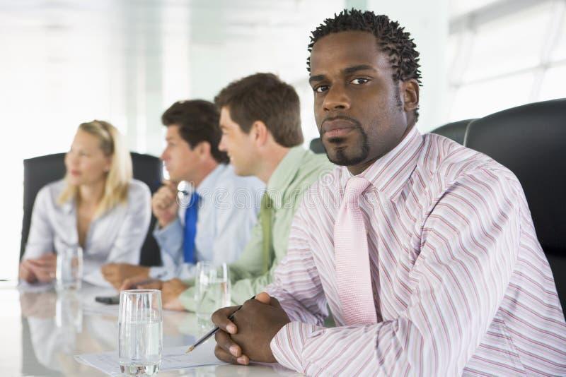 Vier Wirtschaftler in einem Sitzungssaal stockbild