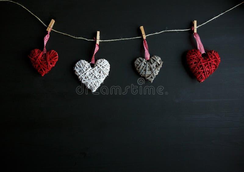 Vier witte en rode harten op zwarte houten lijst Valentijnskaarten, de lenteachtergrond Spot omhoog met copyspace De gelukkige Da royalty-vrije stock foto's