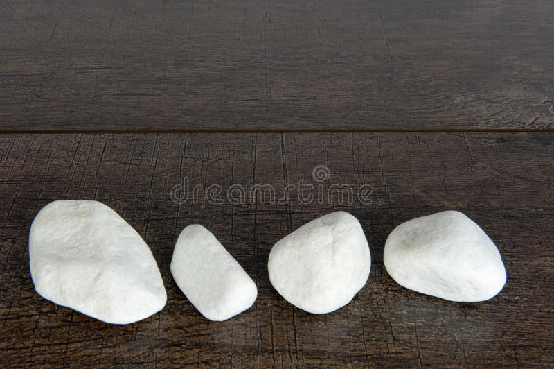 Vier witte rotsen op bruin hout stock fotografie
