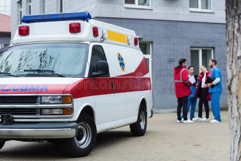 Vier ziekenwagen en artsen die bevinden spreken zich stock foto's