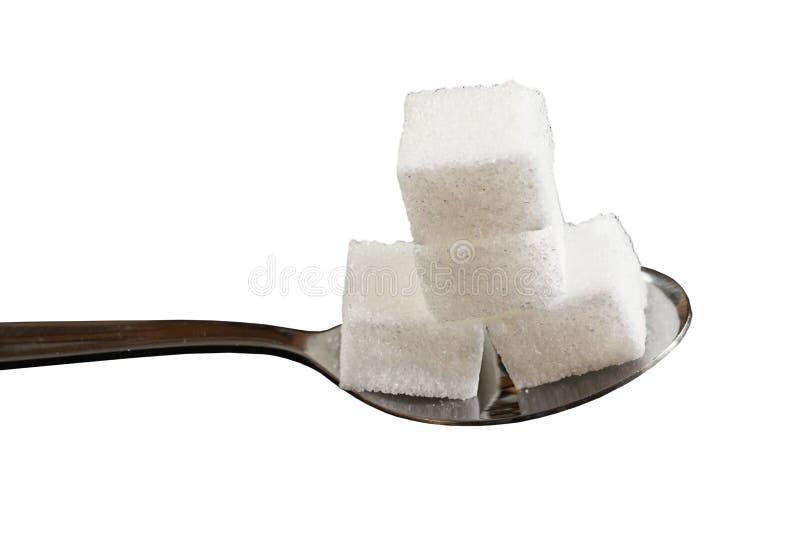 Vier Zuckerwürfel auf einem Teelöffel lizenzfreies stockfoto