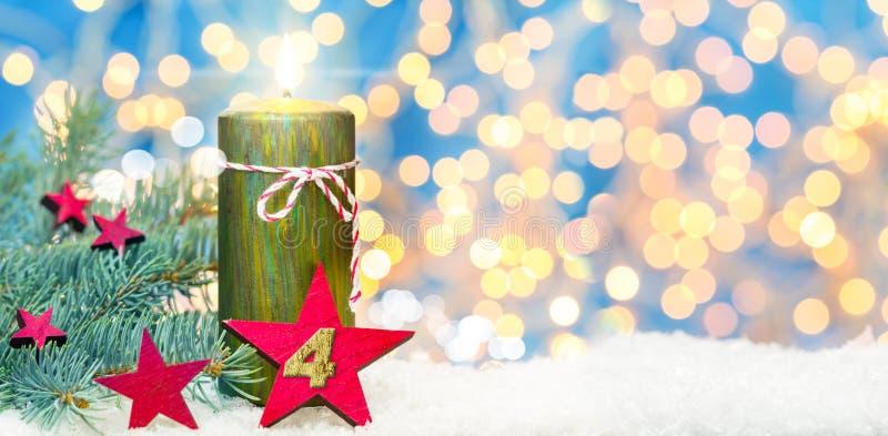Vierde komst, komstdecoratie, kaars en ster in de sneeuw stock foto's