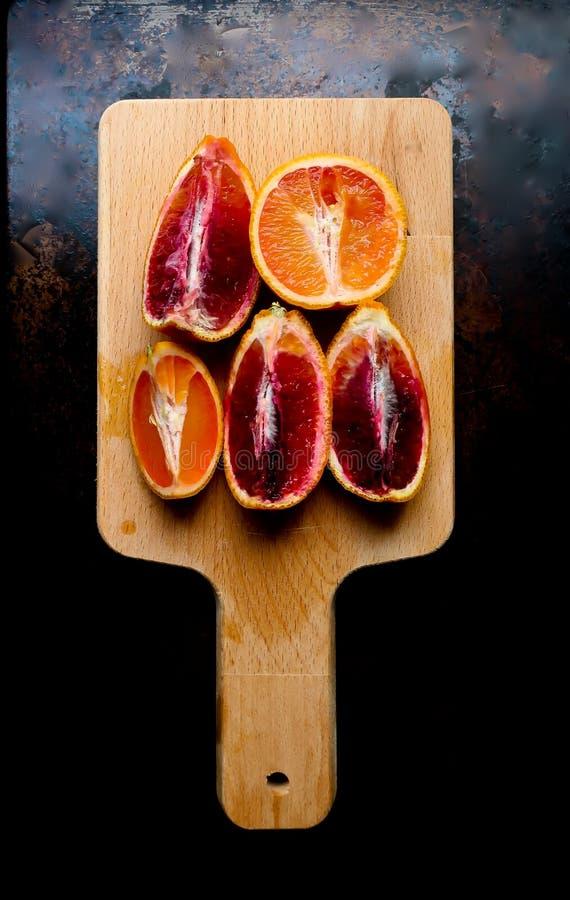In vieren gedeelde bloedsinaasappelen op een houten scherpe raad royalty-vrije stock afbeeldingen