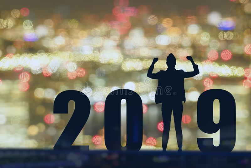 Vierende nieuwe van de de bedrijfs vrijheids jonge hoop van het jaar 2019 Silhouet mens die en zich op de bovenkant van het gebou royalty-vrije stock foto
