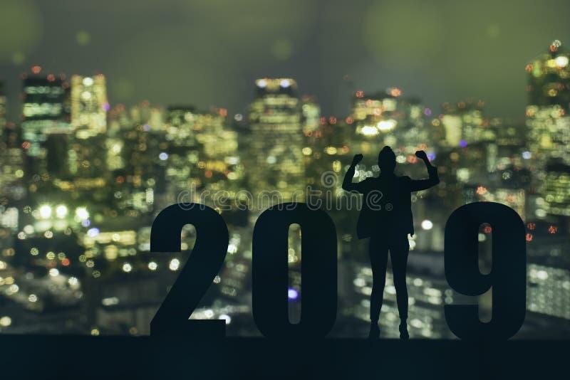 Vierende nieuwe van de de bedrijfs vrijheids jonge hoop van het jaar 2019 Silhouet mens die en zich op de bovenkant van het gebou stock foto