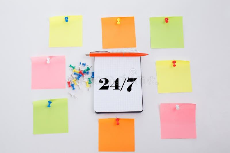 Vierentwintig uren en zeven dagen per week Het concept schrijft op Bureaulijst, blocnote en kleurrijk potlood Mening van hierbove royalty-vrije stock afbeelding