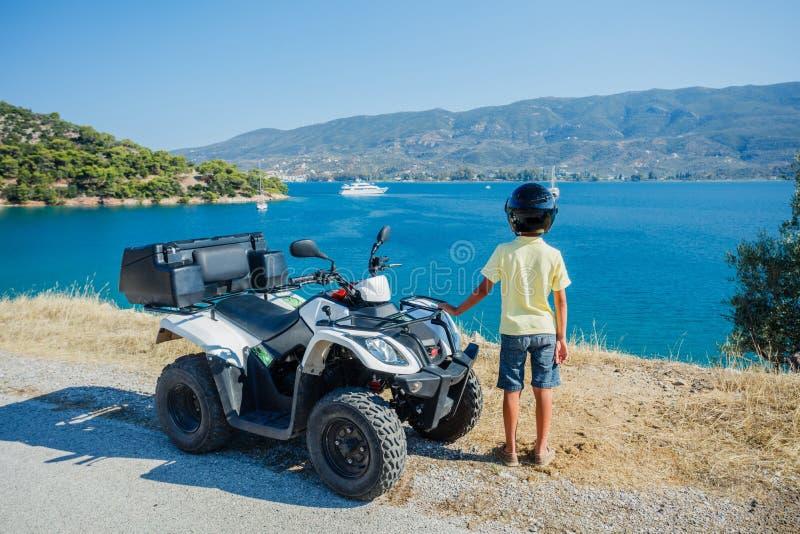 Viererkabelfahrrad des kleinen Jungen Reit Nettes Kind auf quadricycle Bewegungsquersport auf Griechenland-Insel Kindersommerferi lizenzfreies stockfoto