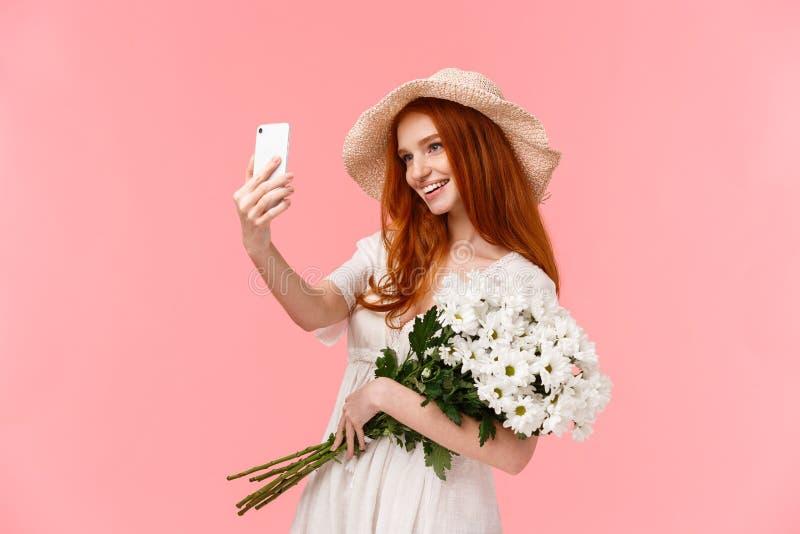 Viering, sociale media en internetconcept Alluring van zadelroodkopvrouwtjes in stro-hoed, lentejurk, bedrijf royalty-vrije stock foto's