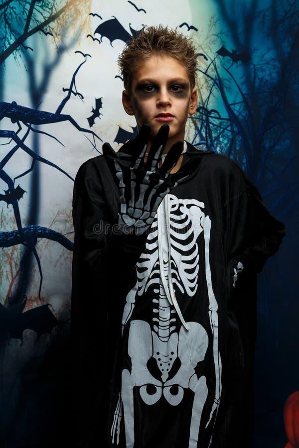 Viering van vakantie Halloween, de leuke 8 jaarjongen in het beeld, kostuum, het skeletthema, de vampier, knuppelconcept stock fotografie