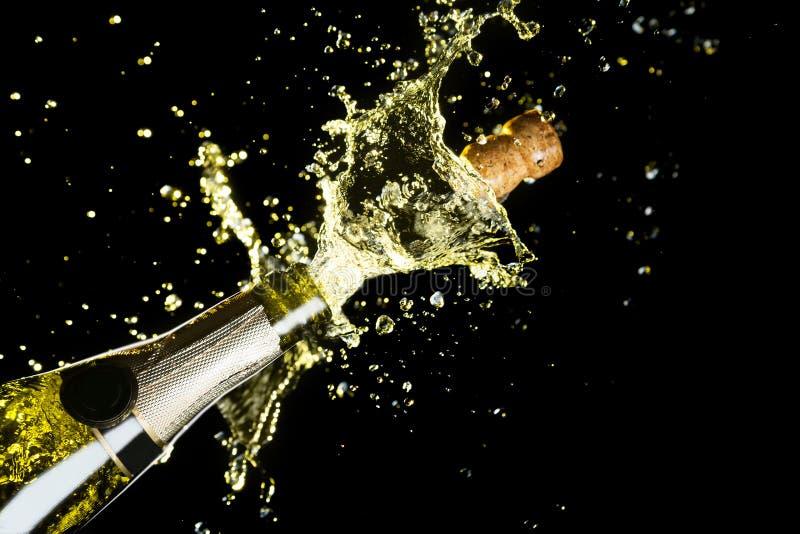 Vieringsthema met explosie van het bespatten van champagne mousserende wijn op zwarte achtergrond stock foto