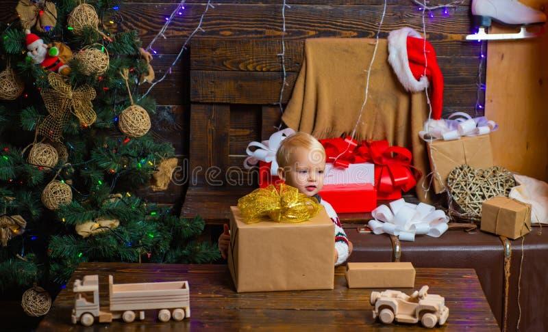 Vieringsvakantie De gelukkige kleine jonge geitjes in santahoed met heden hebben Kerstmis Vrolijk leuk kind die a openen royalty-vrije stock fotografie